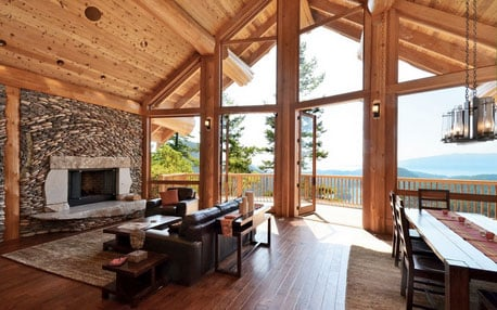 inside log home, bright living room looking onto deck, large post hold up log beams, huge window wall and river rock fire place - gorgeous